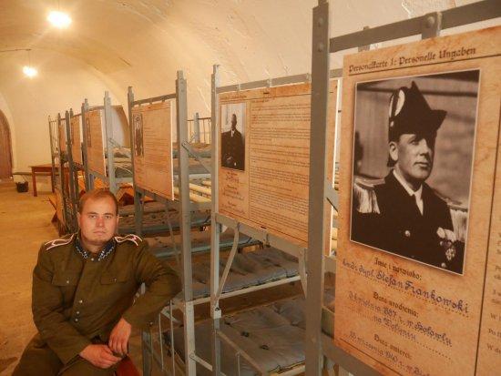 Jedna z sal sypialnych, w których więziono polskich oficerów. Na każdym z łóżek są biogramy z sylwetkami oficerów więzionych w Srebrnej Górze.